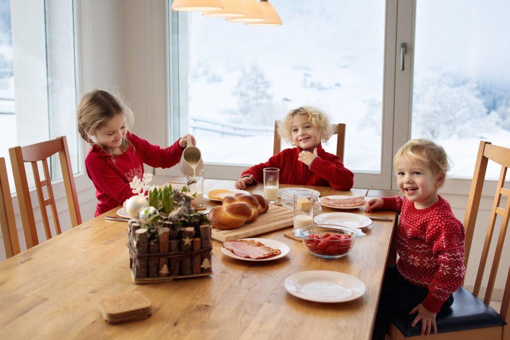 Kids enjoying Christmas morning breakfast in Christmas pajamas