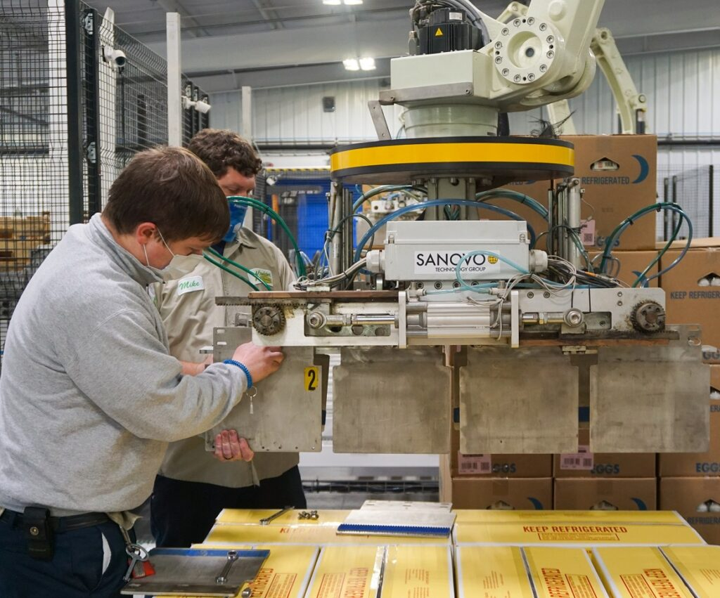 Maintenance Technicians changing panels on a Sanovo Palletizer