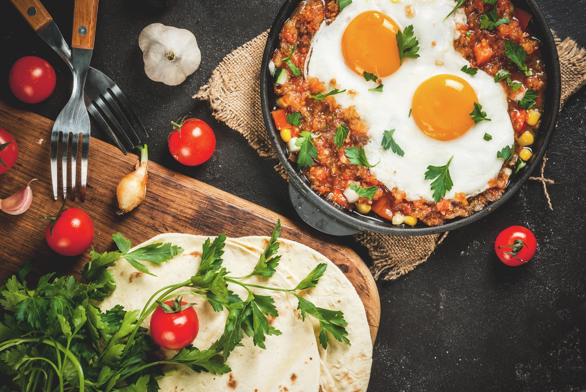 huevos rancheros and tortillas spread out on a table